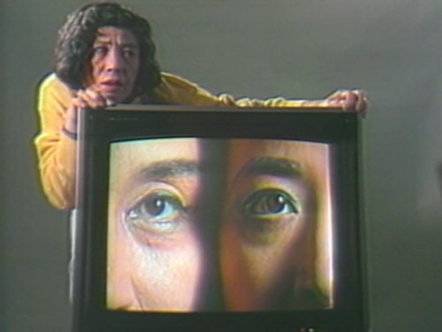 Tv screen with two faces side by side only showing half of each face. Artist behind the tv grasping both side of the screen with their face resting on left hand